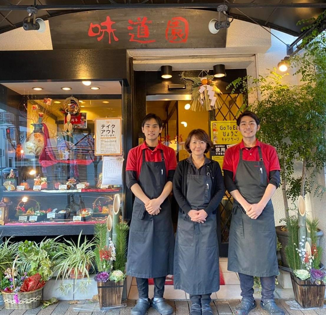 「味道園」の店頭で息子2人と並んで立っている張 珉住さん。