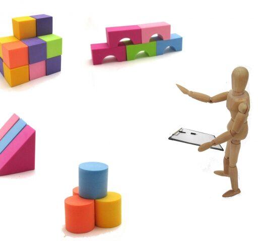 在庫管理のイメージ。人型の小さなフィギュアが各方面に積まれた積み木を指さしながら手元の在庫管理表を照らし合わせている