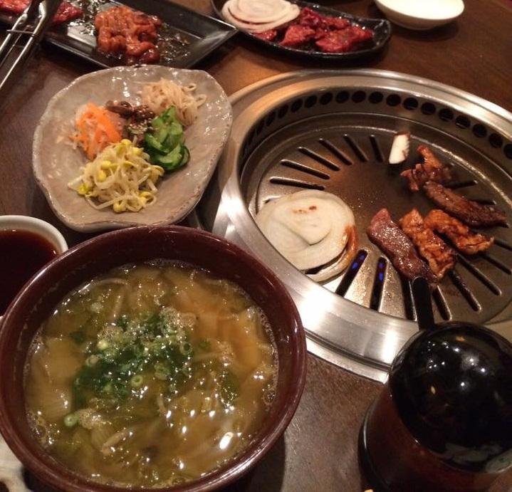 テーブルの上に並べられたチュオタン(どじょうスープ)と焼肉の写真