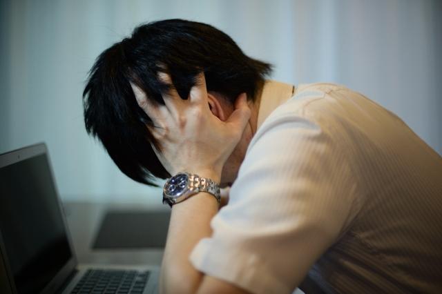 悩んでいるイメージ。男性がノートPCの前で頭を抱えこんで悩んでいる様子
