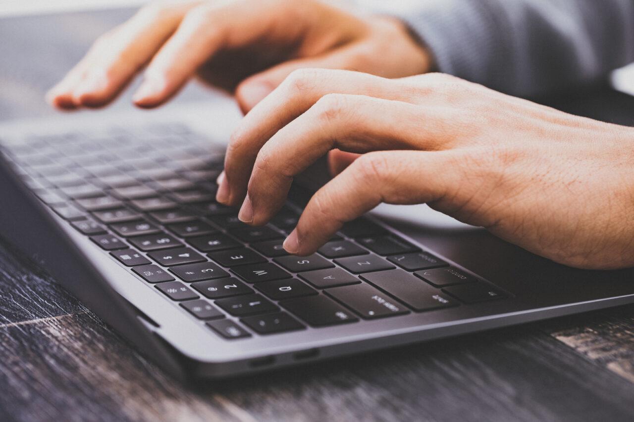 イメージ写真:ノートパソコンでタイピングしている男性の手元