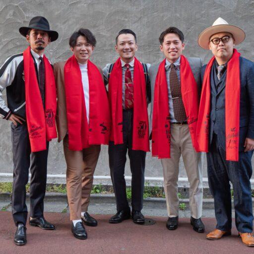 赤いスカーフをした受賞チーム5名が肩を組んでいる写真
