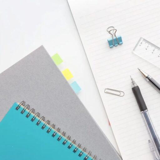 イメージ:机の上に重ねるようにして並べられた文房具。大小のノートやクリップ、ボールペンなど。