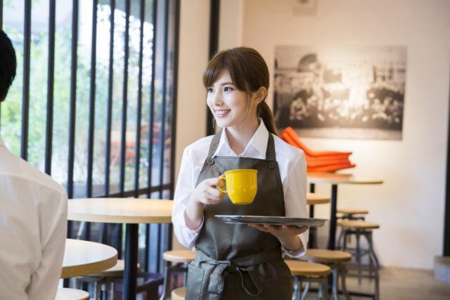 イメージ写真:カフェの店内で紺色のエプロンをつけた女性スタッフが、お客様にカップをお出ししている。