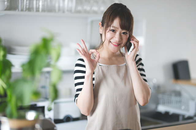 イメージ写真:エプロンを付けた女性スタッフ。電話を耳にあて、こちらに向かって「OK」のポーズ