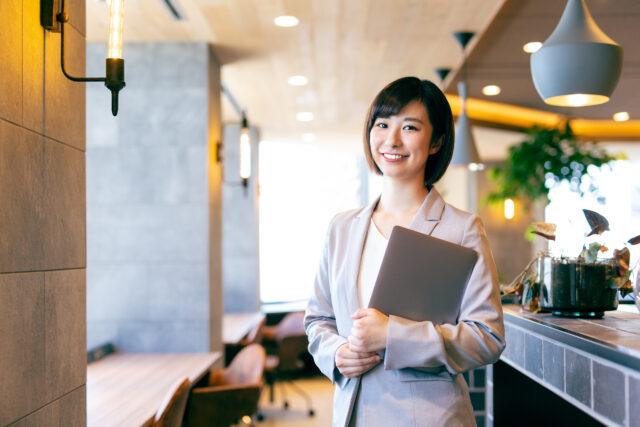 イメージ:飲食店内でこちらを向いて微笑むスーツ姿の女性。手にはバインダーを抱えている。