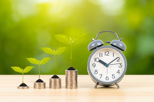 時間の経過とコストのイメージ写真:木のテーブルの上に並べられたコイン。左から階段状に積まれている。その脇には目覚まし時計