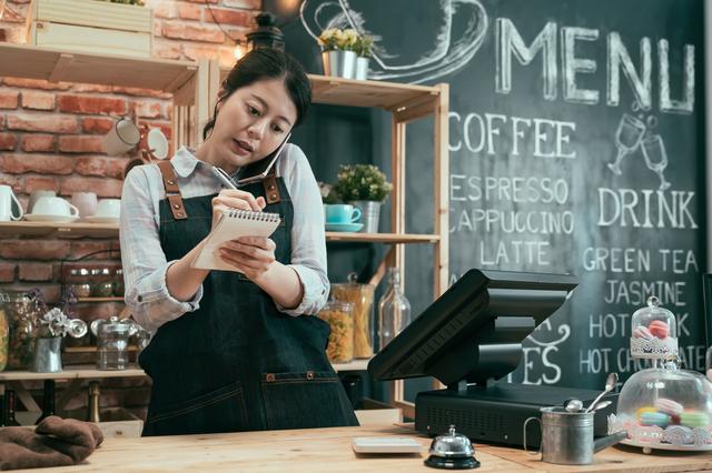 電話予約受付のイメージ写真。電話を肩に挟み、メモを取りながら予約受付をする女性スタッフ