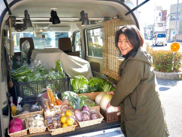 バンの後ろに野菜を並べている角谷さんの写真