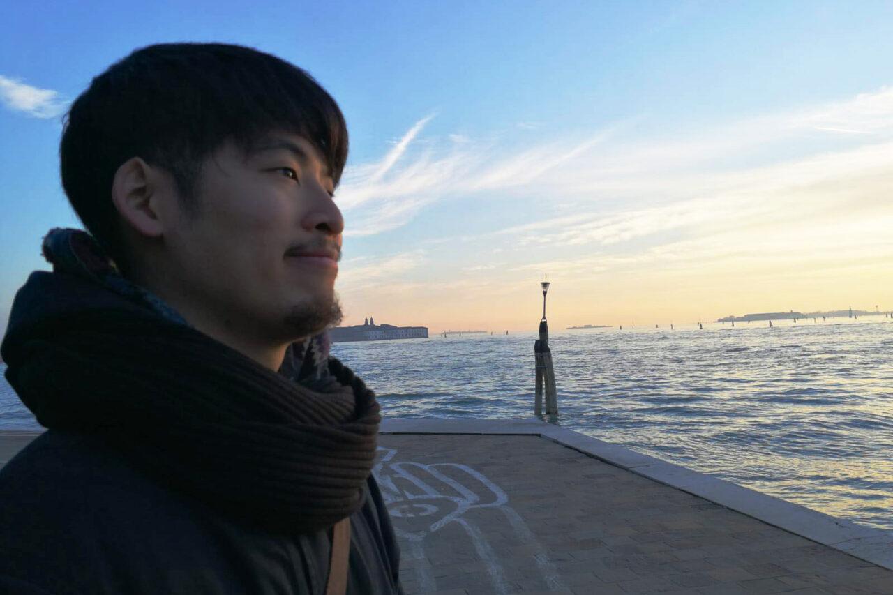 膿をバックにたたずむ吉川さんの写真