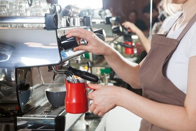 バリスタマシーンを操作してコーヒーを淹れている女性スタッフの手元