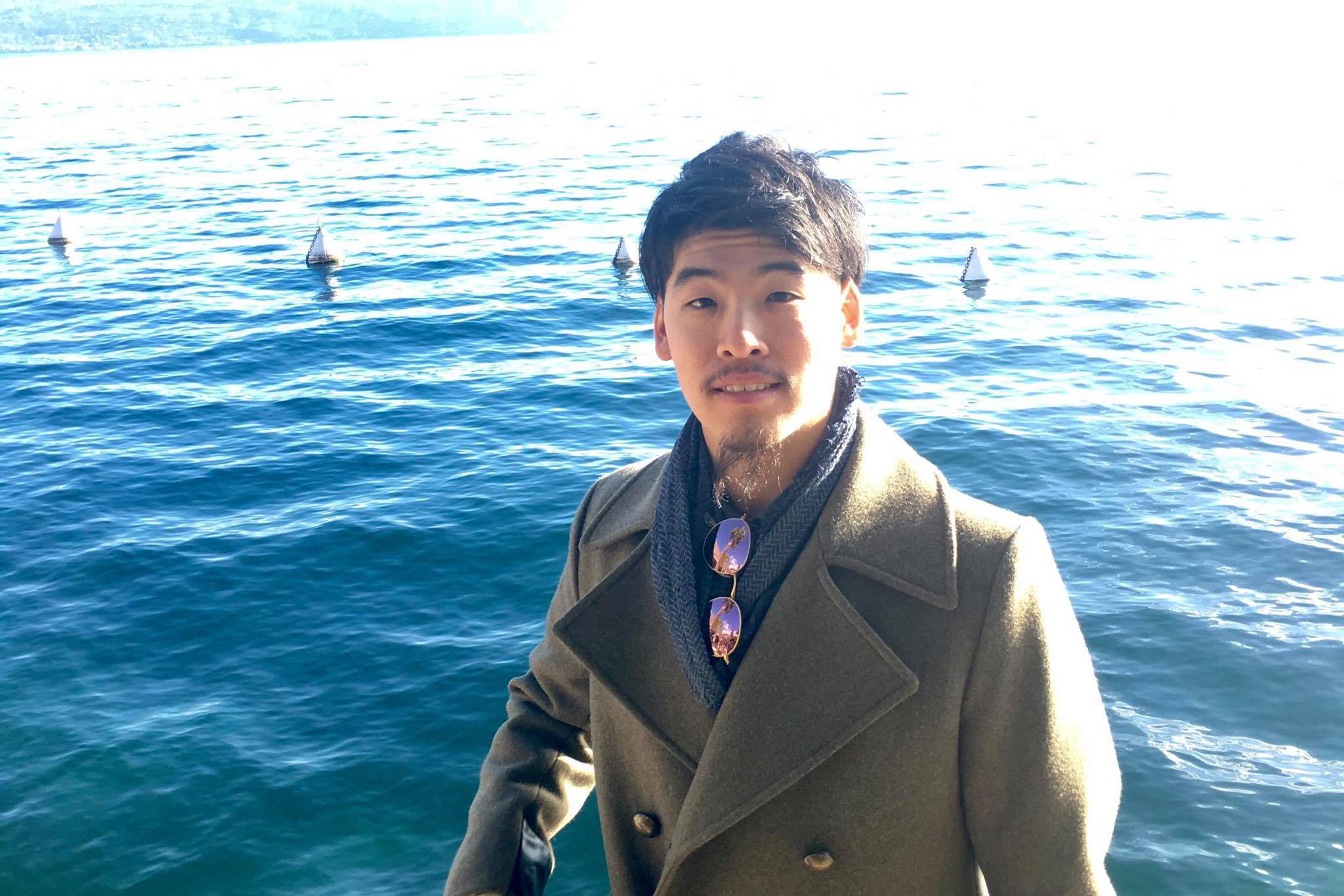海をバックにコート姿の吉川さんのバストアップ写真