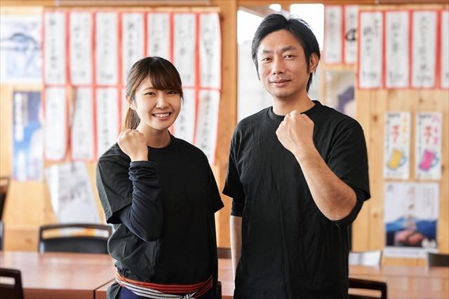 イメージ写真:居酒屋の店内で黒いTシャツを着た二人の男女スタッフがガッツポーズ