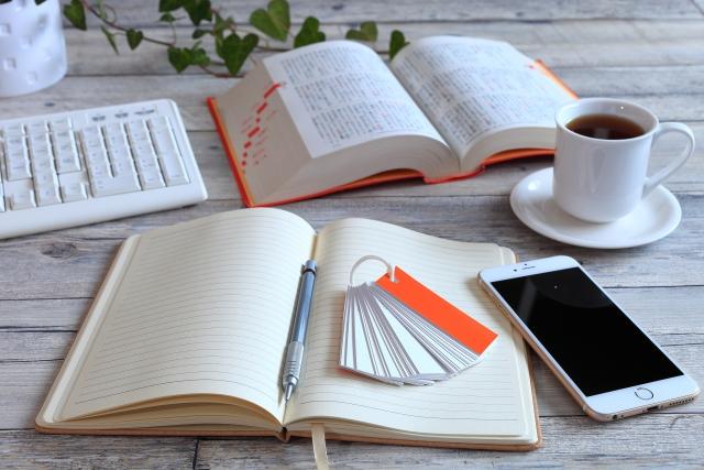 イメージ写真:机の上に置かれた開いたノートや単語帳、開かれた辞書やスマホ