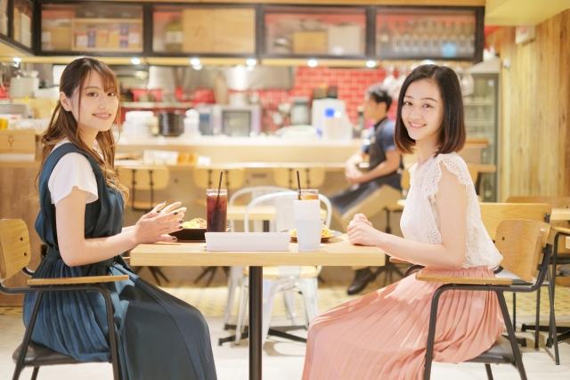 快適な店内のイメージ写真。奥にレストランのキッチンが見える位置に置かれたテーブルに向き合って座る女性客がドリンクを飲みながらこちらに向かって笑っている