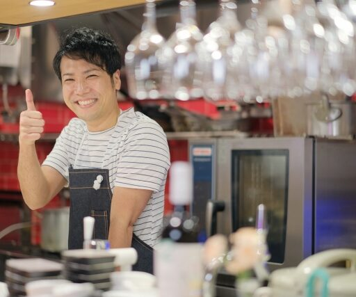 入りやすいお店のイメージ写真。オープンキッチンのカウンター越しに親指を立てて笑顔で微笑みかける、男性店員。