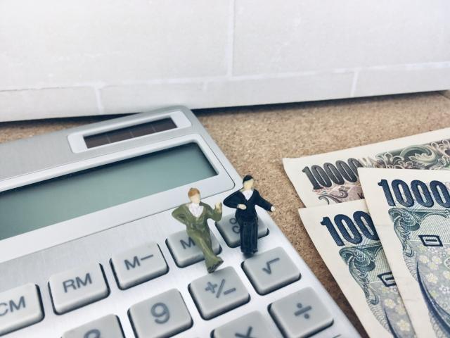 お金の管理のイメージ:電卓の上に座っている小さなスーツ姿のサラリーマンの人形と数枚のお札