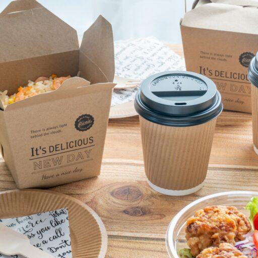 テイクアウト商品のイメージ。厚手のランチボックスに詰められたお弁当や、コーヒーカップなど