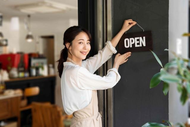 イメージ写真:カフェの店頭で「OPEN」のプレートをかける女性スタッフ