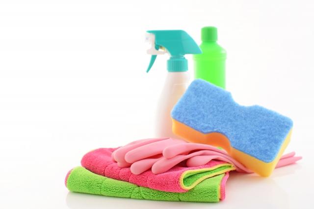 掃除用具のイメージ:スプレーボトルや洗剤ボトル、ピンク色のゴム手袋やスポンジなどカラフルな掃除道具がきれいに並べられている。