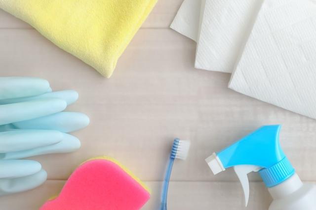 イメージ:机の上に並べられたスポンジやゴム手袋、ダスター、スプレーボトルなどの掃除道具