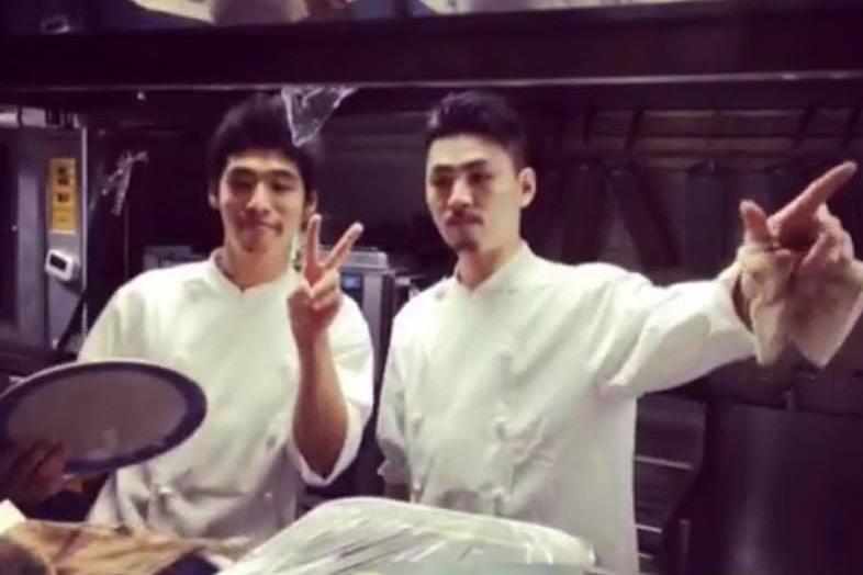 池袋の「AL TEATRO(アル テアトロ)」の調理場で仲間と2人で写るコックコート姿の吉川さんの写真
