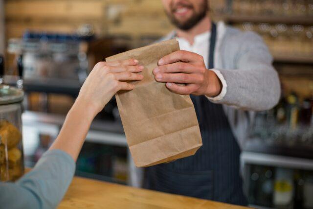 テイクアウトのイメージ写真。カウンター越しに男性スタッフが紙袋に入れた商品を女性客に渡している風景