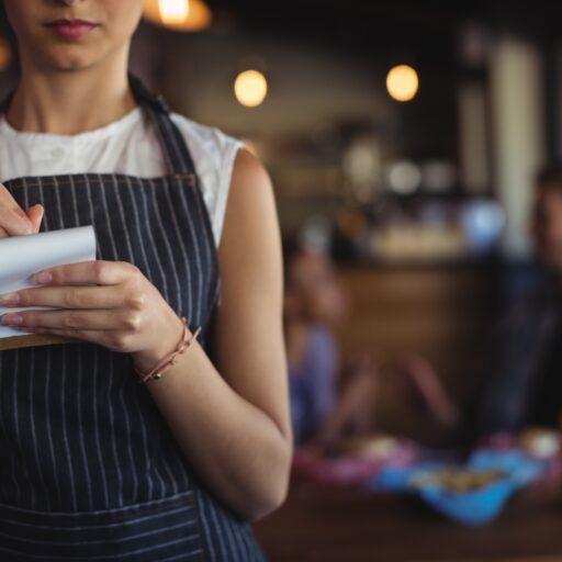 黒いエプロンを付けた女性スタッフがメモ帳を持ってオーダーを聞いている写真