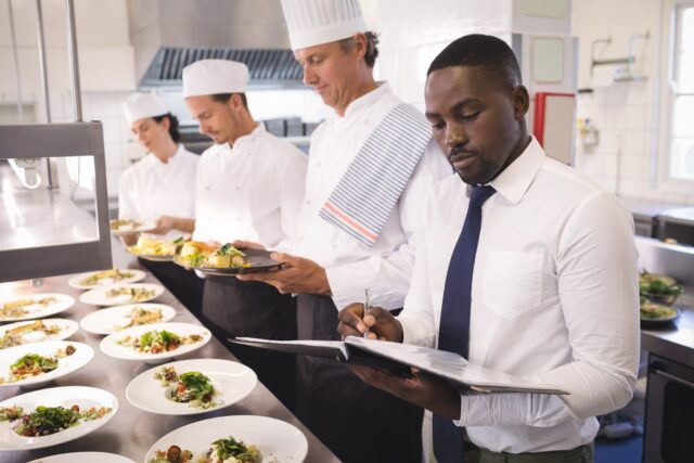 レストランのマネージャーと料理人たち。作られた料理を前にマネージャーがバインダーに何か書き込んでいる様子