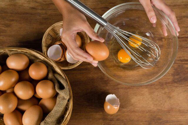 アレルギーのイメージ写真:木のバスケットから卵を取り出し、ガラスのボウルに割って入れている様子