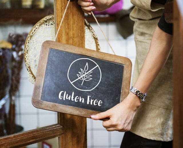 グルテンフリーのイメージ写真。レストランの入り口にかけられた小さな黒板に「Gluten Free」と描かれている