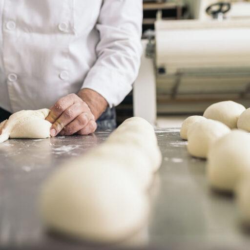 イメージ写真:厨房でパンの生地を切り分けて並べているようす