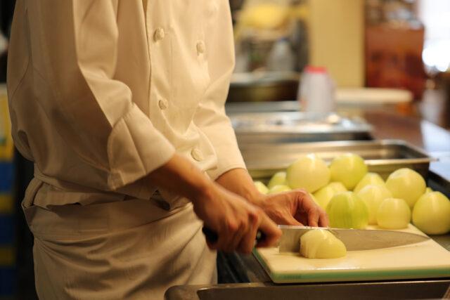 イメージ写真:厨房で野菜をカットしている料理人さんの手元。