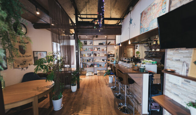 イメージ写真:木のぬくもりを感じるカフェの店内左側には木の丸いテーブルがある席、右側にはバーのようなカウンターテーブル、奥の突き当りには本棚がある