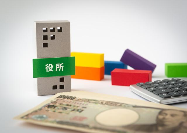 役所での手続きイメージ写真。ビルのような形の積み木に「役所」という看板が貼られており、手前には紙幣が置かれている。