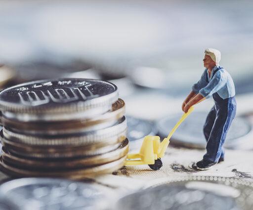 お金の運用イメージ。積み重ねられた500円玉を小さなフィギュアがキャリーカーで引っ張っている。