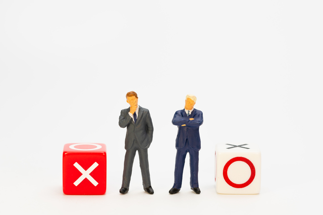 ○×のイメージ写真。中央には考える様子のスーツを来たサラリーマンの人形。それぞれ両サイドには、赤い「×」の箱と白い「○」の箱
