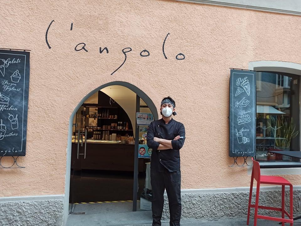 マスクをつけた奥田さんが「L'Angolo(ランゴロ)」のエントランスで腕組みをして立っている