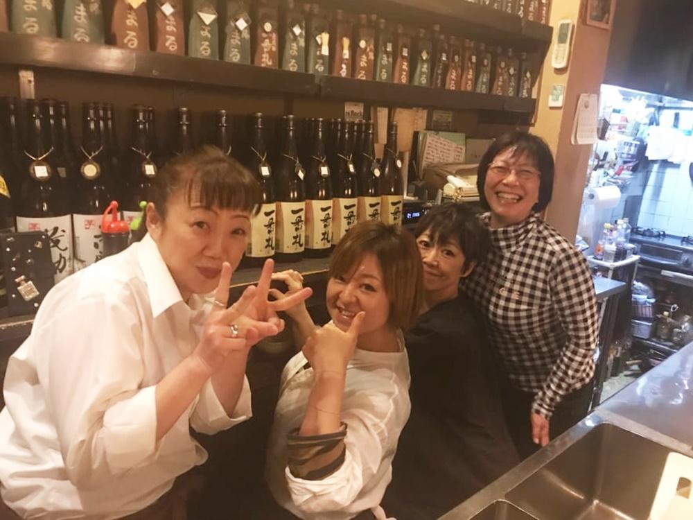 店内カウンターの中でスタッフの女性4名が笑顔でピース