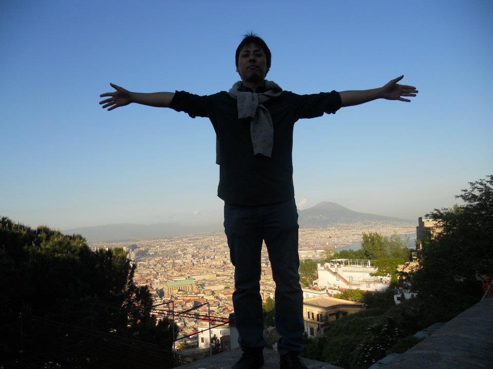 両手を広げて高いところで街並みをバックに撮られた奥田さんの写真
