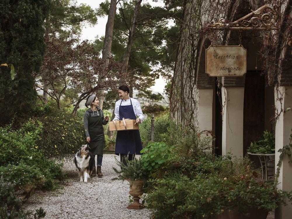 緑豊かな庭を犬と歩く森山さんと小百合さん