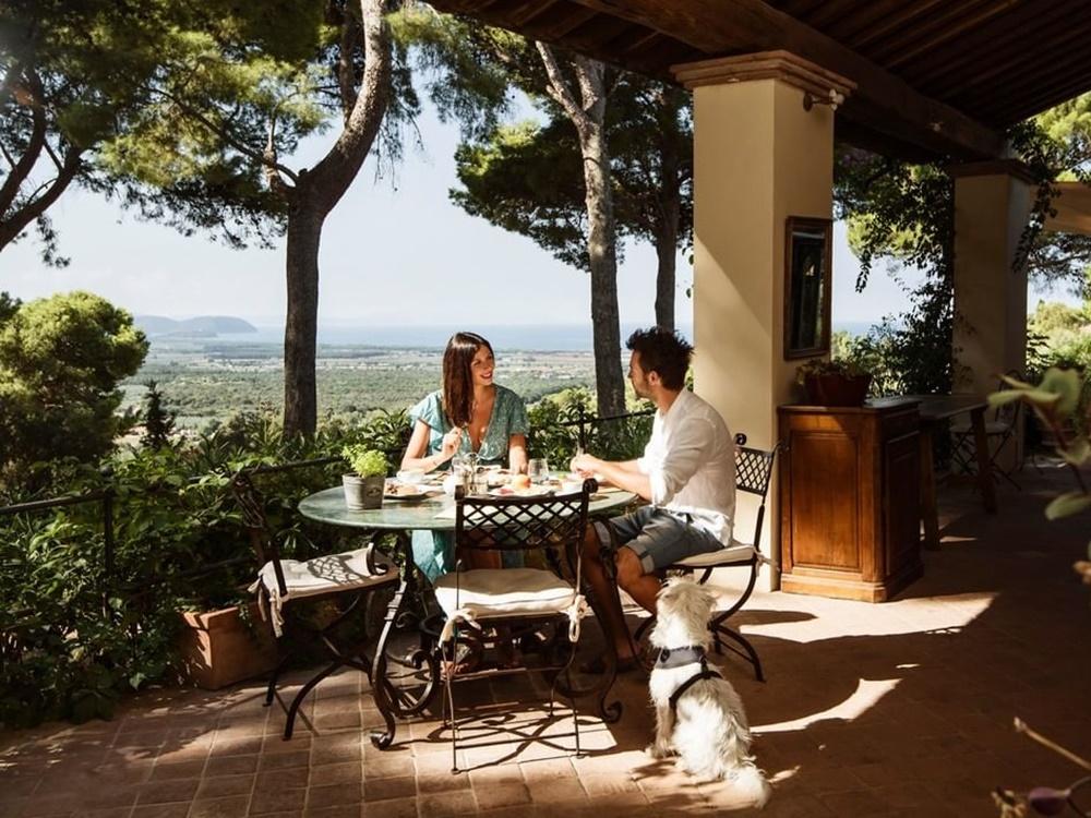 地中海とサンヴィンチェンツォの街を背に男女が食事をしている