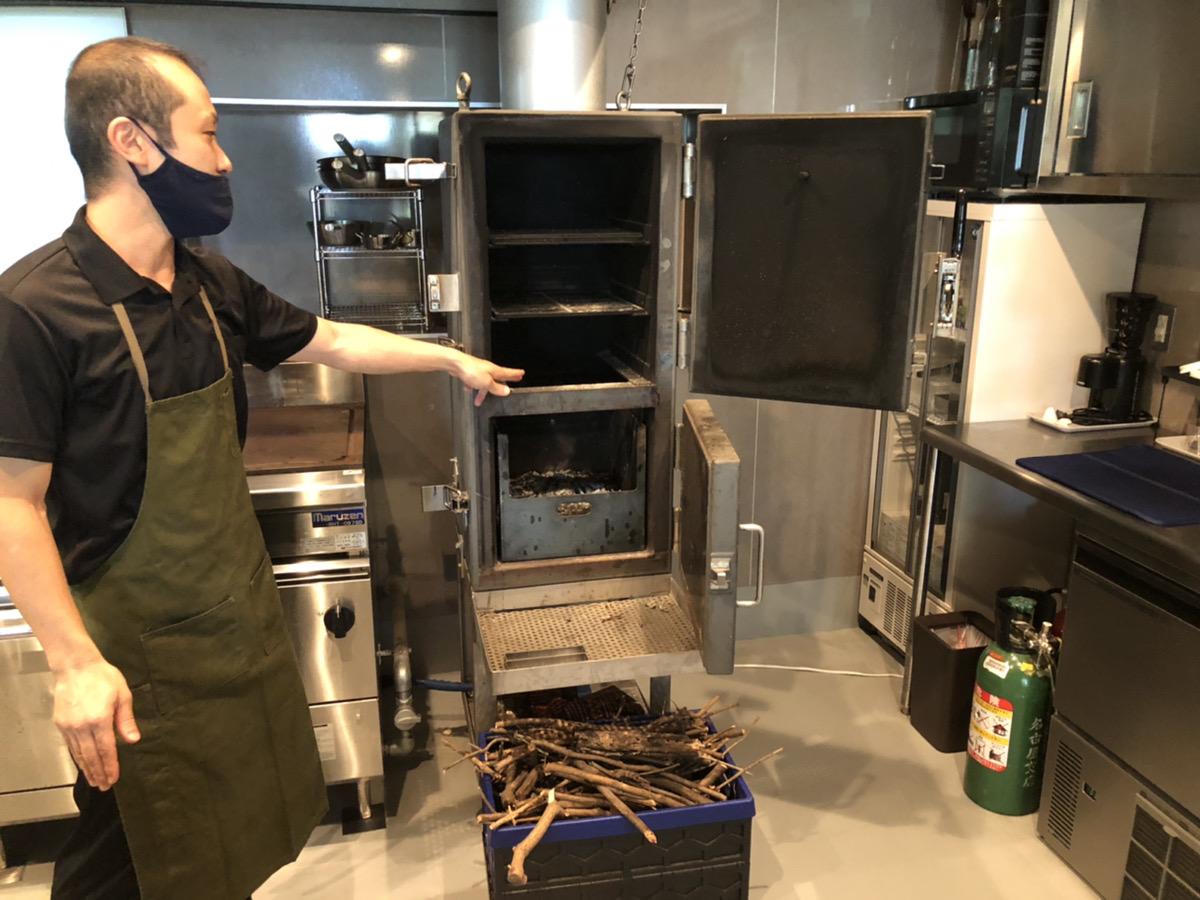 設計した薪を使ったオーブンを指さす菱田さん